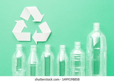 Plastic bottles and recycling symbol. Five bottles on green background.