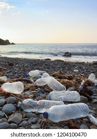 Plastic bottles washed on the atlantic shoreline or beach polluting the environment in northern spain