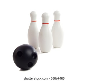 A plastic bowling ball rolling towards three pins, isolated against a white background