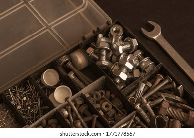 Plastic box with a variety of metal fasteners. Old and new bolts, nuts, screws and screws. Industrial background with copy space. Tinted photo. Selective focus.