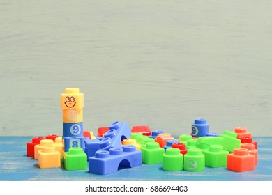 plastic bricks at the table.  Early learning. stripe background. Developing toys