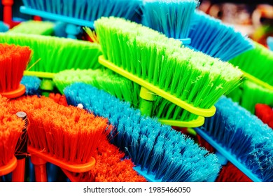 Plastic brushes for cleaning premises. Assortment of multi-colored brooms in the store. Close-up