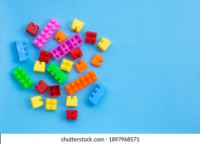 Plastic building blocks on blue background.