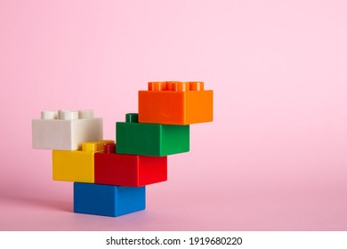 Plastic building blocks on pink background