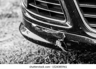 The plastic bumper of a black car cracked. Fiberglass properties in car parts.
