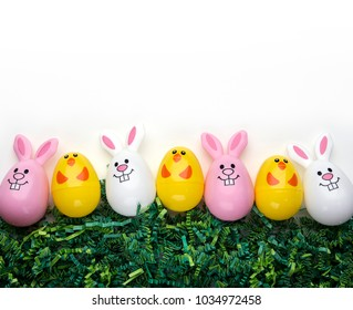 Plastic bunny and chick eggs on green grass