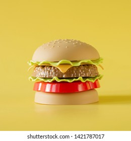 Plastic burger, salad, tomato, meat with on yellow background. Children's toy. Concept of harmful artificial food. Plastic. Not organic. Not useful.