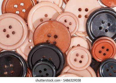 Plastic Buttons. Childrens creative art and craft play background image. Simple brown cream pink and black painted discs for kids creativity.