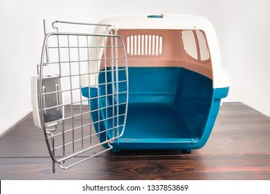 Plastic cage carrying for dogs and cats on a wooden table. Travel transportation, veterinary clinic and pet care concept