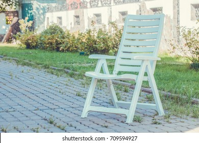 Plastic chair in garden. Outdoor. Toned photo.