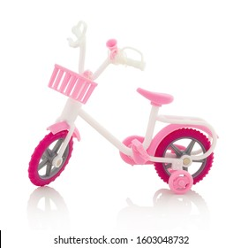 Plastic childish girly bicycle toy, with basket near handlebars. With rack and auxiliary wheels. Isolated on white background with shadow reflection. With clipping path. With vector path. Pvc bike
