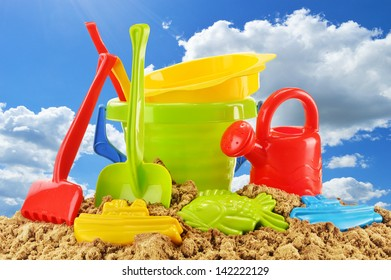 Plastic children toys for playing in sandpit or on a beach over the blue sky