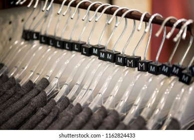 Plastic clothes hangers on a rack, different sizes