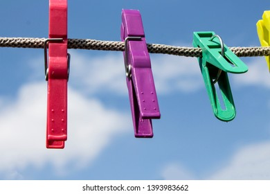 Plastic clothespins. Linen clothespins on a rope against a bright blue sky. Sunny bright summer day. Copy space