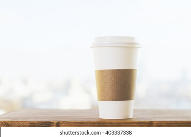 Plastic coffee cup on wooden desktop and blurry white background. Mock up