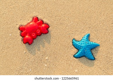 Plastic colored shapes for children play with sand on the beach. Baby plastic molds lying in the sand on the seabeach. Two bright summer toys - red crab and blue starfish in the sand in sunny day.