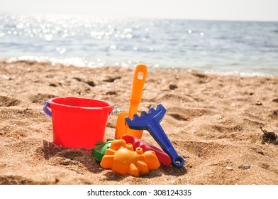Plastic colored toys on the beach