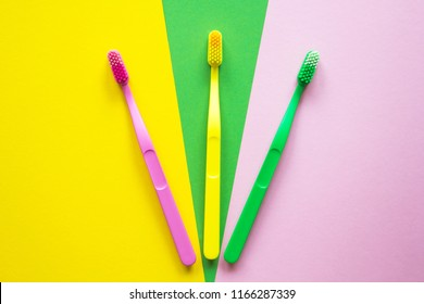 Plastic colorful toothbrushes on yellow, green, pink background. Colour concept.
