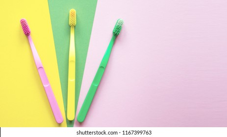 Plastic colorful toothbrushes on a yellow, green, pink background. Dental care concept.
