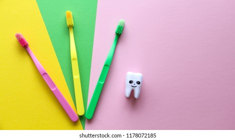 Plastic colorful toothbrushes and smiling tooth on a yellow, green, pink background. Dental care concept. Teeth care minimalism concept.