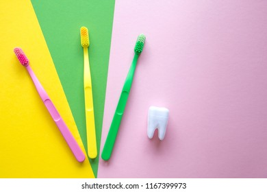 Plastic colorful toothbrushes and white tooth on a yellow, green, pink background. Dental care concept.