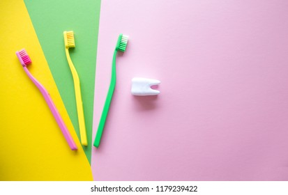 Plastic colorful toothbrushes and white tooth on a yellow, green, pink background. Dental care concept. Teeth care minimalism concept.