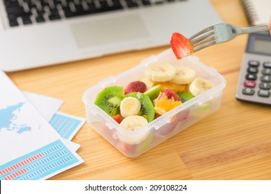 Plastic container with fruit salad and a fork on the desk, selective focus