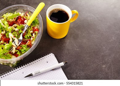 Plastic container of portion of pasta salad with yellow fork in it and one mug of coffee on the dark desktop surface