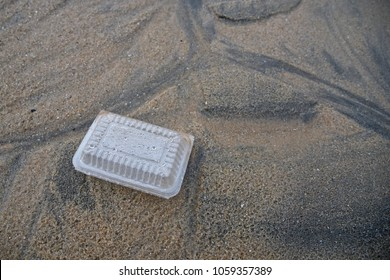 Plastic container  washed up on sandy beach. Unpleasant beach pollution and danger to wildlife and marine fish stocks.