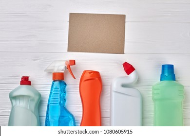 Plastic containers with cleaning liquid. Set of house cleaning supplies on white wooden table with paper card for text. Spring cleaning concept.