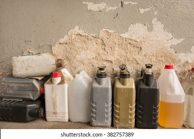 Plastic containers, oil can, grunge bottles and tanks in a workshop.