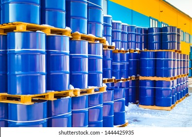 Plastic containers palletized near the stock. Barrels for toxic substances. Chemical storage tanks. Barrels for shipment from stock. Transport of hazardous liquids. Warehouse work. Chemical industry.