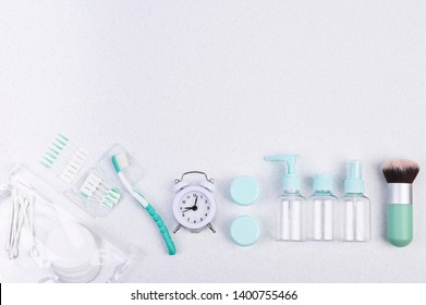 Plastic containers, toothbrush and alarm clock for travel on a white background. Flat lay.