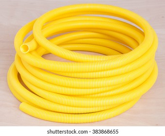 Plastic corrugated pipe color yellow on the wooden floor.