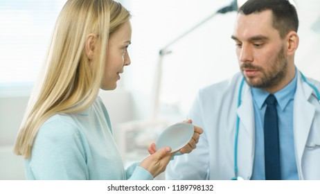 Plastic / Cosmetic Surgeon Shows Female Patient Breast Implant Samples and Talk About Her Future Surgery. Modern Hospital with Technologically Advanced Medical Equipment.