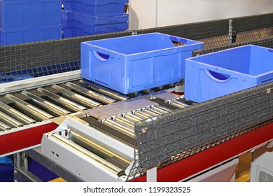 Plastic Crates at Conveyor Belt Rollers in Factory