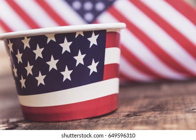 Plastic cup with american flag on the wooden table.