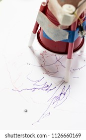 Plastic cup with DC motor and batteries writing with a marker on white sheet of paper. STEAM educational activity for children at school. An autonomous robot that writes made by children with waste