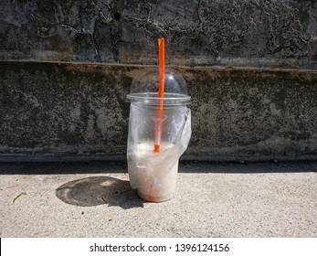 Plastic cup with dirty water after drink on the walkway roadside. The people throwing trash carelessly in anywhere not a bin. Environment negligently concept.