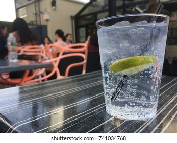 Plastic cup of gin and tonic on a rooftop bar in the city. People enjoying an after work drink. Gin and tonic with lime and ice on a table at outdoor rooftop bar.