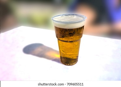 Plastic cup of light beer on a white table. Disposable glass.