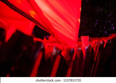 Plastic cup on a red light fence/Abstract and symbolic image of a plastic cup left on a red lit fence.