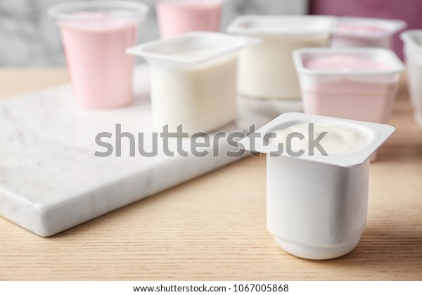 Plastic cup with tasty yogurt on table