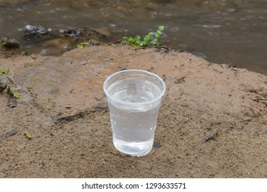 plastic cup with water on the sand near the river