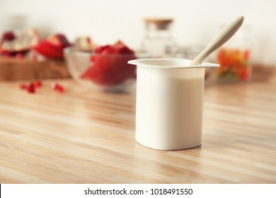 Plastic cup of yummy yogurt on wooden table