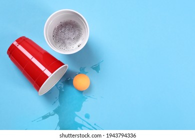 Plastic cups and ball on light blue background, flat lay. Beer pong game