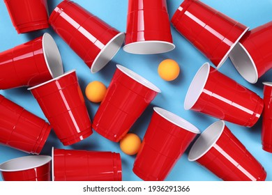 Plastic cups and balls for beer pong on light blue background, flat lay