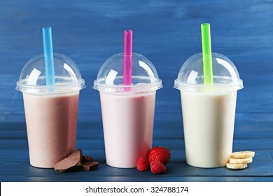 Plastic cups of milkshake on color wooden background