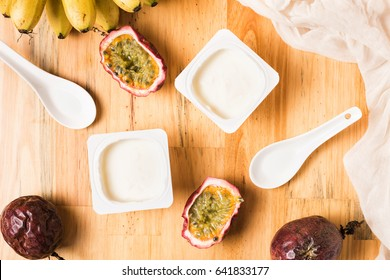 Plastic cups with yogurt on wooden background. Breakfast with bananas,  passion fruits and  yoghurt. White spoon and napkin on table. Top view