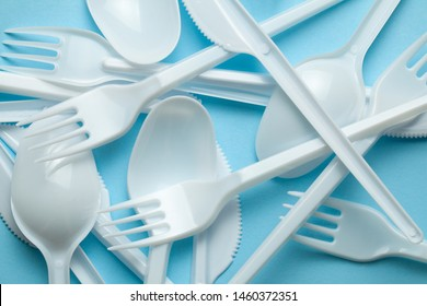 Plastic cutlery, forks, spoons and knives. Pollution of the environment with plastic and microplastics. Blue background.